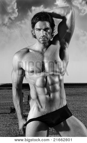 Fine art black and white portrait of a beautiful muscular male model in black briefs in provocative pose outdoors
