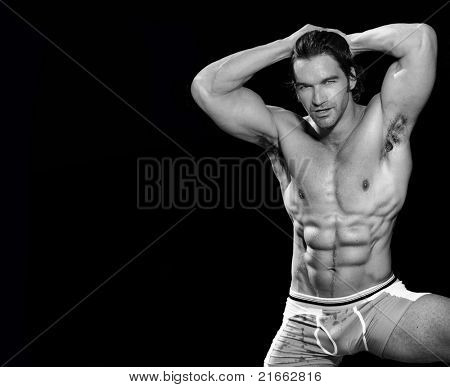 Black and white fine art  portrait of a sexy male fitness model posing and flexing with lots of copy space