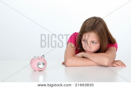 Portrait of young girl looking at piggy bank