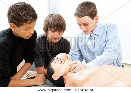 Teenage boys learn CPR life saving techniques on a mannequin.