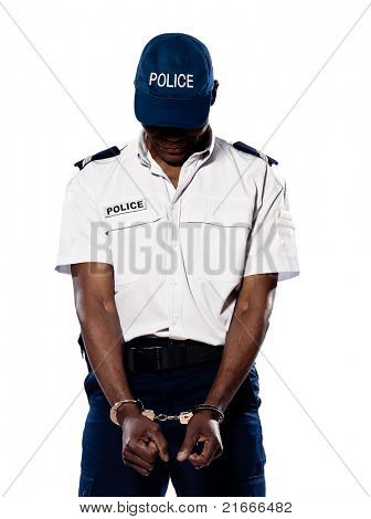 Hand cuffed police officer with head down standing on white isolated background