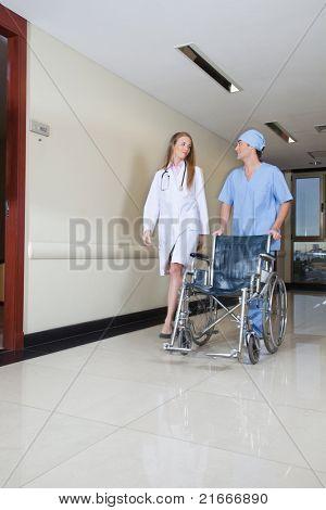 Doctor walking with male nurse pushing wheelchair