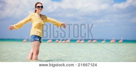 Young beautiful woman at shallow tropical water with pink flamingos on background