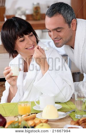 a woman giving a teaspoonful of yoghurt to his husband at breakfast, both are wearing bathrobes