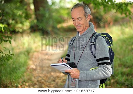 sixty years old man taking notes on a forest trail