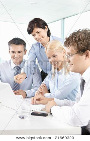 Group of business partners listening to mature woman explaining her idea at meeting