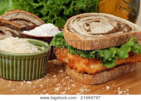 Freshly breaded and deep fried cod fillet on marble rye bread with lettuce on wooden cutting board.  Seasoned breadcrumbs and flour included in composition.  Macro with shallow dof.