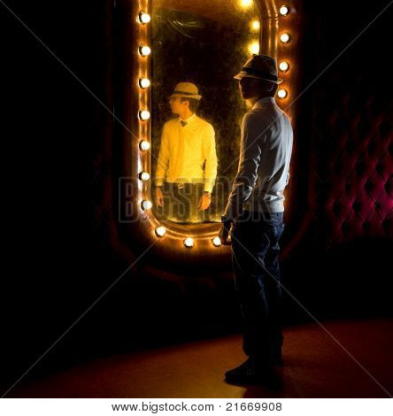 fashionable young man looks at himself in mirror