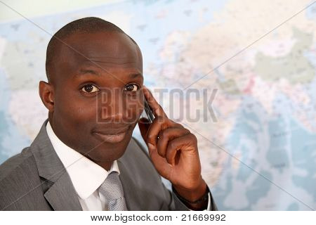 Businessman talking on the phone with worldmap in background