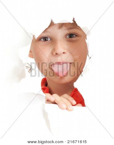 funny kid showing tongue in torn paper hole isolated