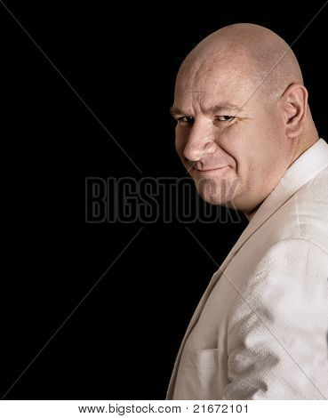 Portrait of a wise charming smiling shaved headed man turning around with smirk