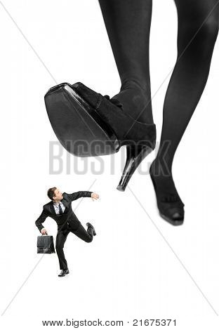 Afraid businessman running away from a big foot isolated on white background