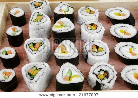Maki Sushi and Sashimi - California Roll with Avocado and Salmon, Cream Cheese and Raw Salmon inside. on wooden plate . isolated over white background