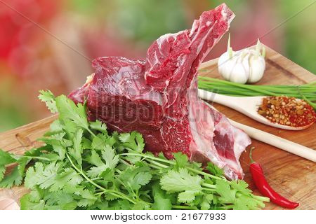 raw meat : fresh beef pork big rib piece with garlic and green stuff on wood isolated over white background