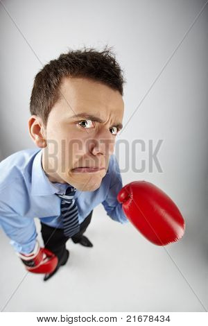 Fisheye of displeased businessman in boxing gloves looking at camera