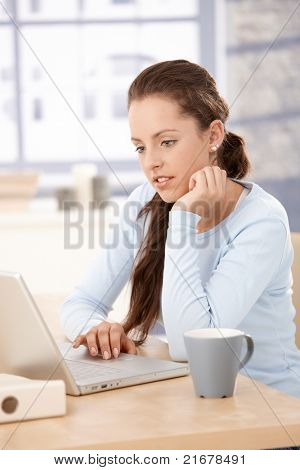 Pretty girl working at home, using laptop, looking at screen, sitting by table.?