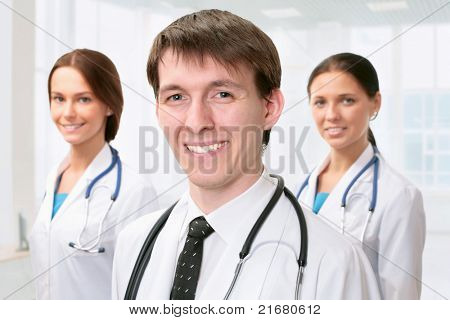 Young doctor standing in front of his team and smiling