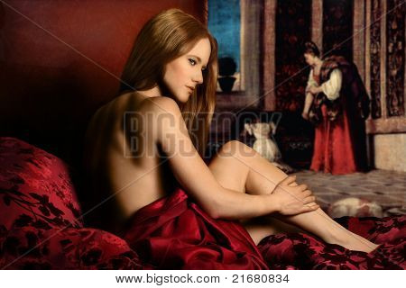 Portrait of beauitful nude young woman in bed with classical painting in the background