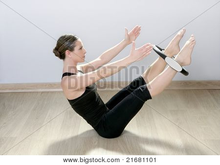beautiful instructor woman with magic pilate ring in sport gym
