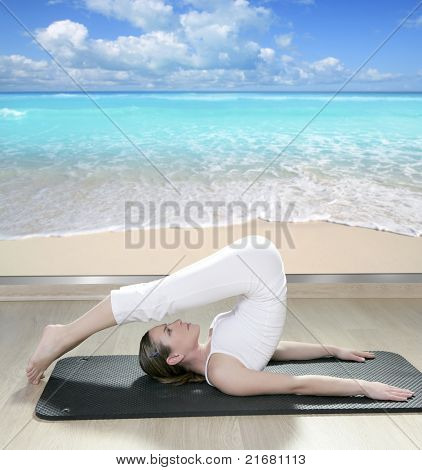 beautiful woman in black mat yoga in front a window view of tropical beach