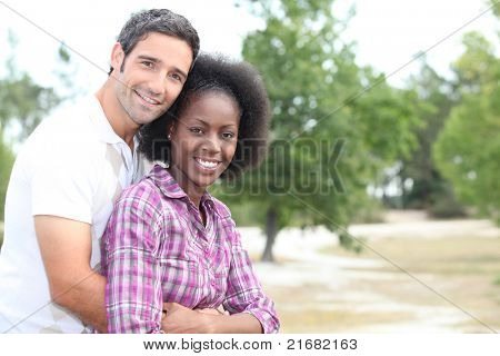 Mixed race couple hugging in the countryside