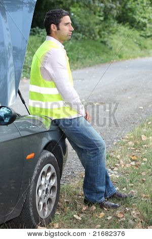 Man sat by broken-down car