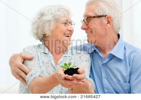 Elder smiling loving couple holding fresh green sprout, symbol of good bank investments for the retirement