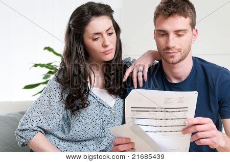 Casal jovem, lendo uma lei financeira ou carta com expressões preocupados em casa
