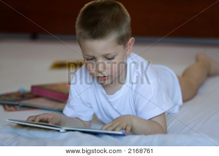 Child Reading A Book Lying Down On A Bed