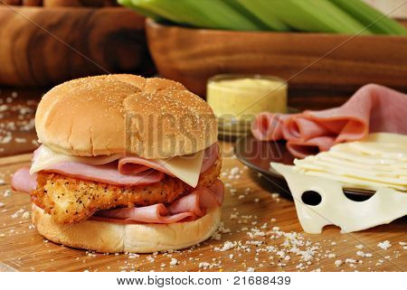 Freshly prepared chicken cordon bleu sandwich on wood cutting board with breadcrumbs.  Swiss cheese, ham, honey mustard, and celery in soft focus in background.  Macro with shallow dof.