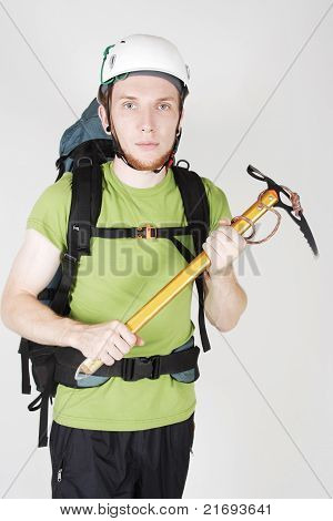 Mountain Tourist In Helmet And With Big Backpack Standing And Holding Pick