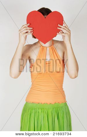 Young Girl In Bright Clothes Holding Valentine Heart Card Before Her Face
