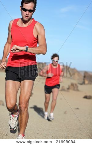 Running sport. Man runner looking at heart rate monitor watch during adventure marathon run in beautiful desert landscape.