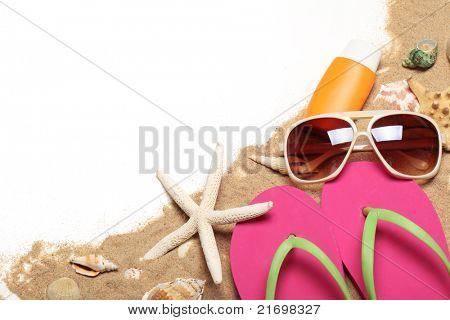 Flip flops,sunglasses,sunblock,seashells with sands,Copy space for your text.