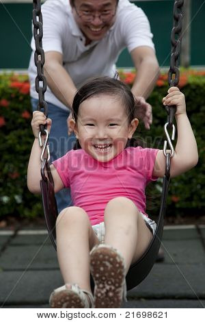 Laughing little girl on swing with her father