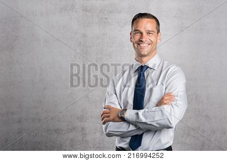 poster of Happy businessman looking at camera on grey background with copy space. Handsome young business man