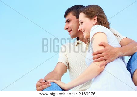 Photo of peaceful couple looking forward with blue sky on background