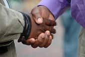 image of say goodbye  - Two African American men shaking their black hands as a sign of big friendship and to say goodbye - JPG