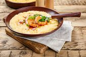 Plate with fresh tasty shrimp and grits on wooden table poster