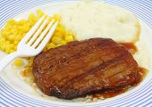 stock photo of frozen tv dinner  - Close view of a Salisbury steak meal with corn and potato on a blue striped plate with white fork - JPG