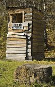 stock photo of outhouses  - Old wooden poorly constructed outhouse with humorous signs - JPG