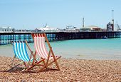 stock photo of beachfront  - deck chairs on the beach Brigton England on a sunny day - JPG