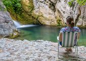 A Dreamy Girl Is Meditating In A Green Lagoon Near A Waterfall. poster