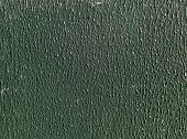 image of stippling  - Sunlight highlights green stippled paint on board - JPG