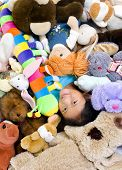 stock photo of mating bears  - A young girl is in the middle of a big pile of stuffed animals - JPG