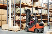 stock photo of forklift driver  - warehouse worker driver in uniform loading cardboard boxes by forklift stacker loader - JPG
