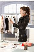Young attractive fashion designer talking on phone by desk in office, working.