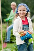 Gardening - little girl with mother working in vegetable garden