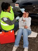 Female paramedic attending to a young car crash victim (the sleeve badges have been replaced by a no