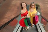 Beautiful women with shopping bags on escalator at strip mall poster